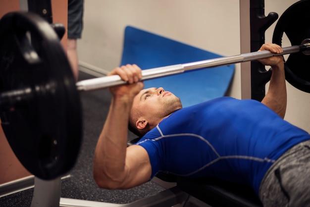 Skupiający się mężczyzna robi treningu na ławce wagi