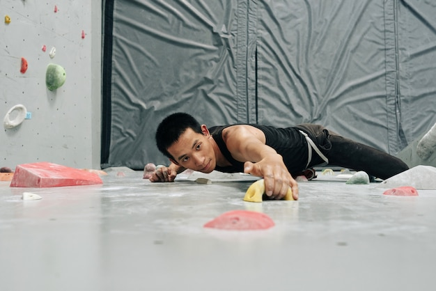 Skupiający się mężczyzna wdrapuje się na ścianę