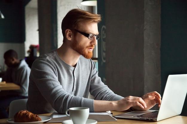 Skupiający się millennial rudzielec mężczyzna używa laptopu obsiadanie przy kawiarnia stołem