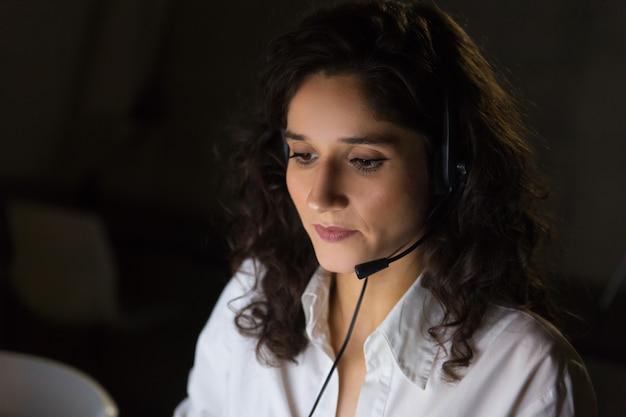 Skupiający się młody bizneswoman w słuchawki