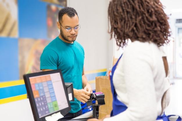 Skupiający się młody człowiek płaci rachunek w sklepie