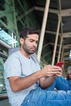 Skupiający się młody podróżnik patrzeje smartphone