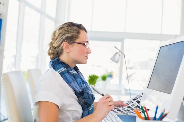 Skupiający się młody redaktor pracuje przy jej biurkiem