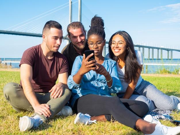 Skupiający się młodzi przyjaciele używa smartphone plenerowego