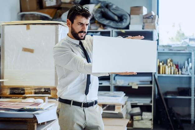 Skupiający się poważny caucasian brodaty nadzorca patrzeje dowód w kostiumu i krawacie podczas gdy stojący w drukarni.