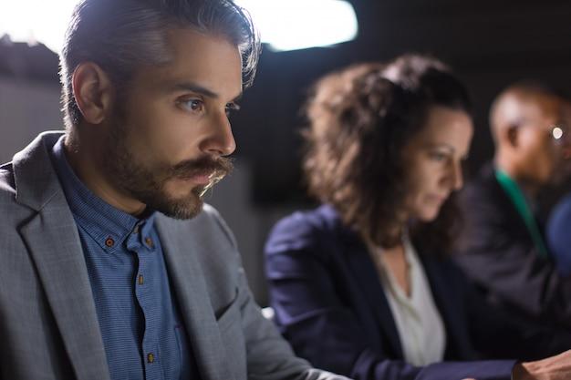 Skupiający się przystojny biznesmen patrzeje laptop