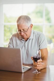 Skupiający się starszy mężczyzna używa laptop i pijący wino w domu