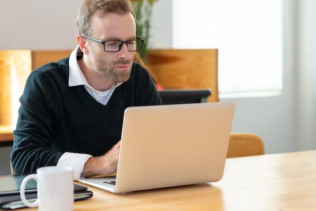 Skupiający się w średnim wieku biznesowy mężczyzna pracuje na laptopie.