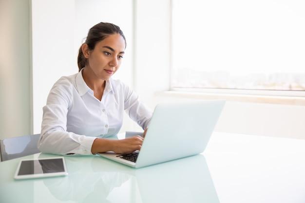 Skupiający się żeński profesjonalista pracuje na komputerze