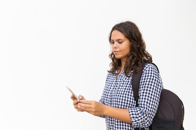 Skupiający się żeński turysta z plecakiem i telefonem komórkowym