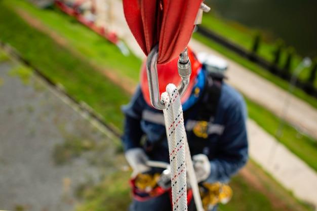 Skupić się widok z góry mężczyzna pracownik dół wysokość zbiornika węzeł dachowy poręcz dostęp linowy kontrola bezpieczeństwa grubości zbiornik magazynowy dach propan.