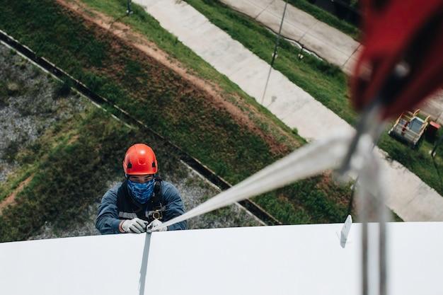 Skupić widok z góry mężczyzna pracownik dół wysokość zbiornika dach dostęp linowy kontrola bezpieczeństwa grubości zbiornika magazynowego propan.