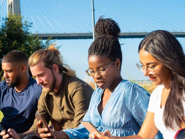 Skupieni przyjaciele za pomocą telefonów komórkowych na zewnątrz