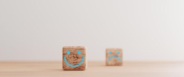 Skupienie się na ekranie wydruku twarzy uśmiechu na drewnianym bloku kostki i rozmycie twarzy smutku na ciemnej stronie dla oceny obsługi klienta i koncepcji nastawienia emocji przez renderowanie 3d.