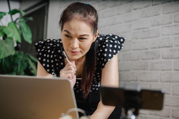 Skupiona azjatka, korzystająca z laptopa w domu, patrząc na ekran, rozmawiając, czytając lub pisząc e-maile.