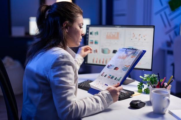 Skupiona bizneswoman sprawdzająca grafikę z nootebooka