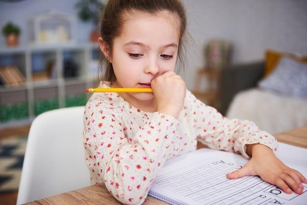 Skupiona dziewczyna odrabiająca pracę domową w domu