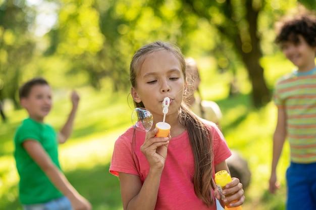 Skupiona dziewczyna robiąca bańkę mydlaną i przyjaciół