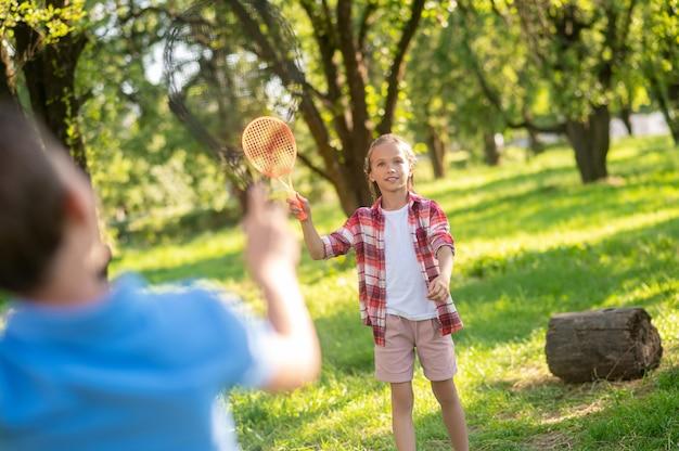 Skupiona dziewczyna z rakietą i chłopcem na plecach