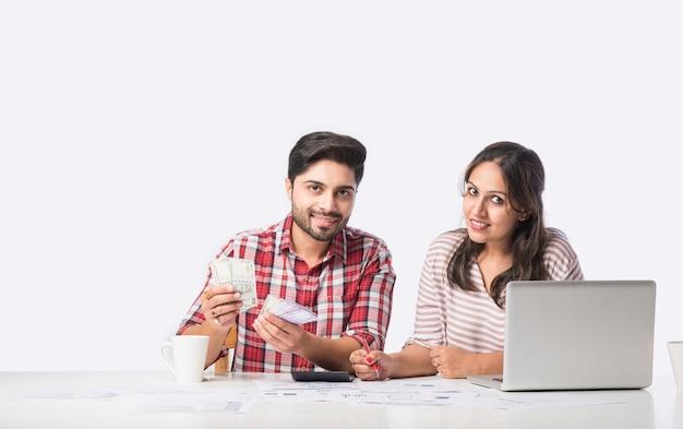 Skupiona indyjska młoda para księgowa, obliczanie rachunków, omawianie wspólnego planowania budżetu za pomocą usług bankowości internetowej i kalkulatora, sprawdzanie finansów