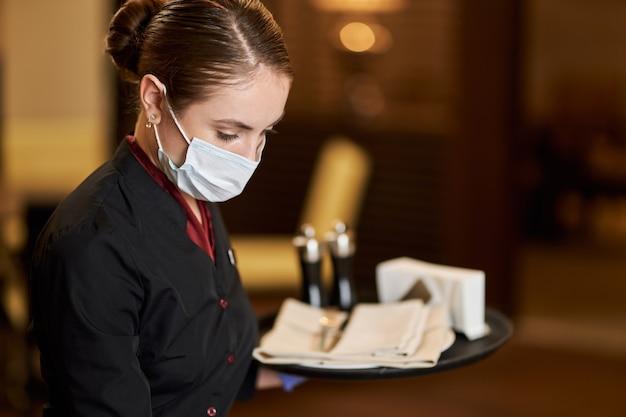 Skupiona kelnerka w masce oddechowej pracująca w kawiarni