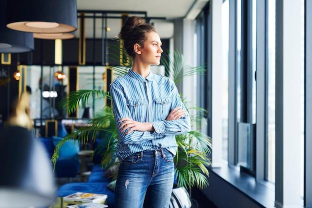 Skupiona kobieta patrząca przez okno w biurze