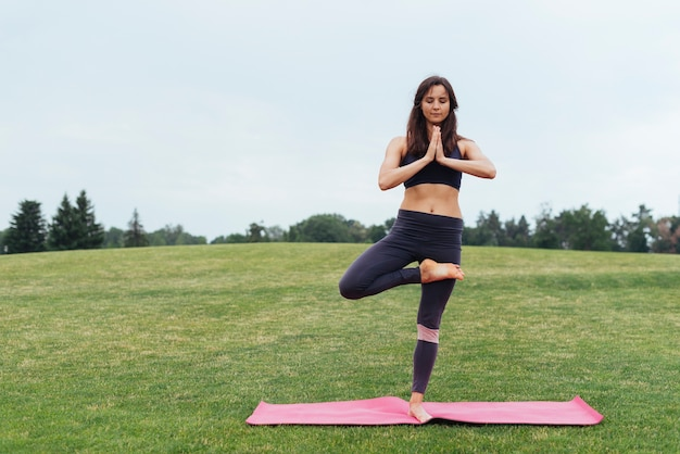 Skupiona kobieta robi joga na zewnątrz