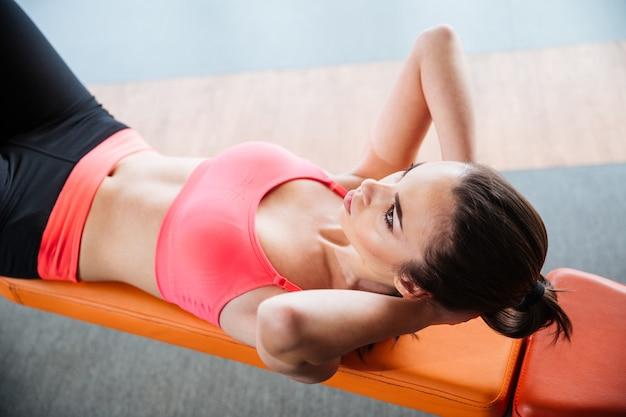 Skupiona ładna młoda sportsmenka robi brzuszki na ławce w siłowni