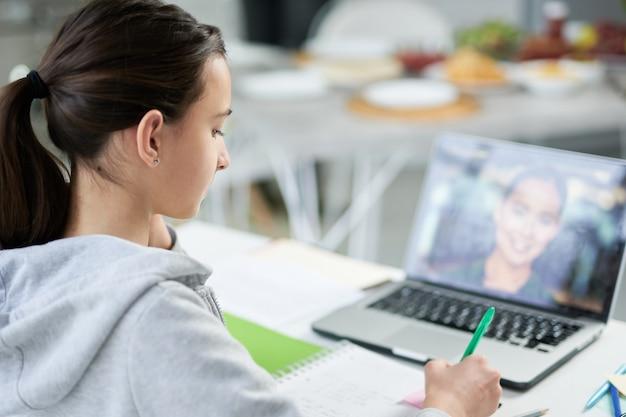 Skupiona latynoska nastolatka pisze w swoim zeszycie podczas lekcji online, za pomocą laptopa, siedząc przy stole w domu. edukacja na odległość, koncepcja edukacji domowej