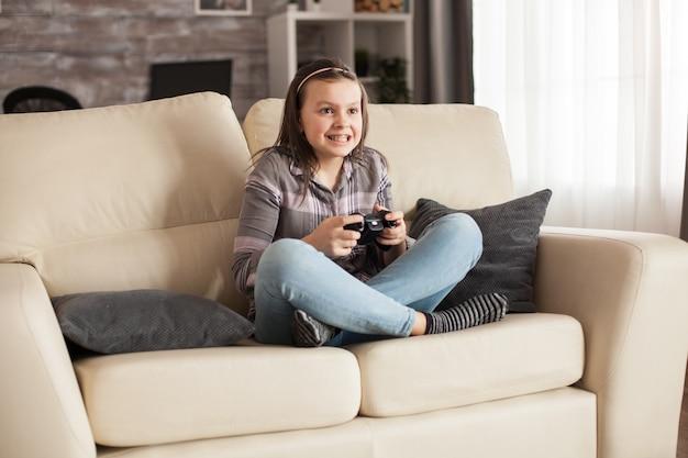 Skupiona mała dziewczynka z szelkami grająca w gry wideo za pomocą bezprzewodowego joysticka.