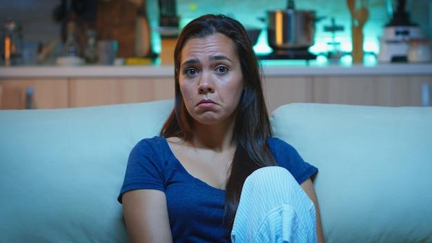 Skupiona młoda kobieta zwracająca uwagę na film ze zszokowanym, skoncentrowanym i zdumionym wyrazem twarzy. emocjonalnie oszołomiona i szerokooka dama reagująca na imponujący i zdumiewający moment w telewizji