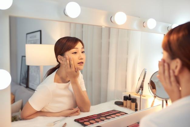 Skupiona piękna młoda azjatka patrząca na siebie w lustrze
