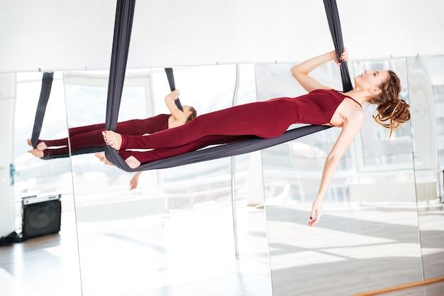 Skupiona piękna młoda kobieta robi jogę antygrawitacyjną w studio