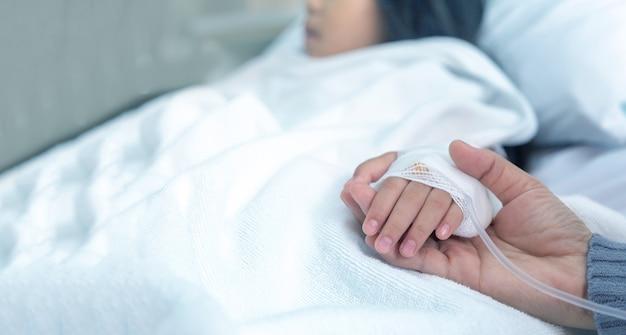 Skupioną rękę trzymającą rękę chorego dziecka i matki na łóżku podłączono do roztworu soli w szpitalu.