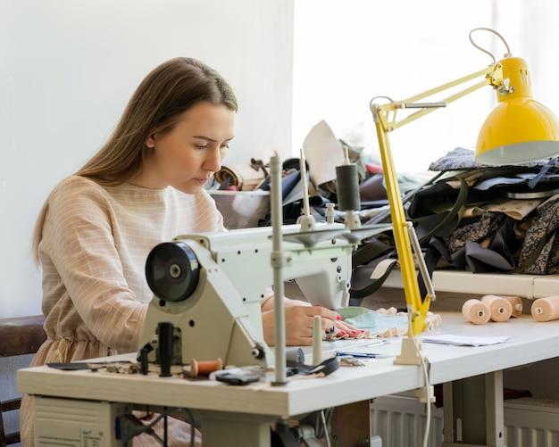 Skupiona szwaczka szyjąca ubrania w swoim miejscu pracy