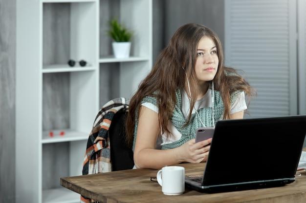 Skupiona uczennica odrabia lekcje w domu, siedząc przy biurku z laptopem