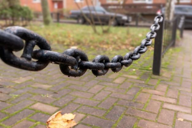 Skupiono się na zawieszeniu metalowego łańcucha, części ogrodzenia.