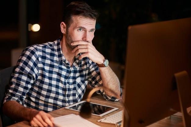 Skupiony biznesmen korzystający z komputera w nocy