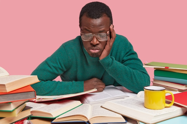 Skupiony ciemnoskóry mężczyzna uważnie przegląda podręczniki, uczy się informacji, nosi duże okulary z powodu złego wzroku, czuje się smutny i znudzony