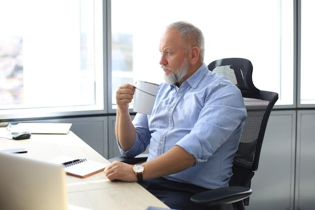 Skupiony dojrzały biznesmen głęboko zamyślony, siedząc przy biurku z filiżanką kawy w ręku w nowoczesnym biurze.