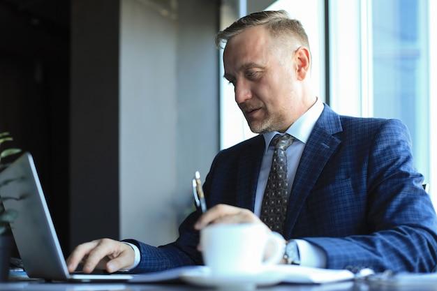 Skupiony dojrzały biznesmen głęboko zamyślony, siedząc przy stole w nowoczesnym biurze.