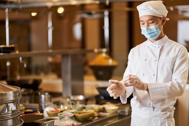 Skupiony kucharz używający rękawiczek w kuchni
