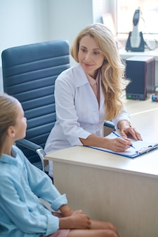 Skupiony lekarz siedzący przy biurku podczas konsultacji pediatrycznej