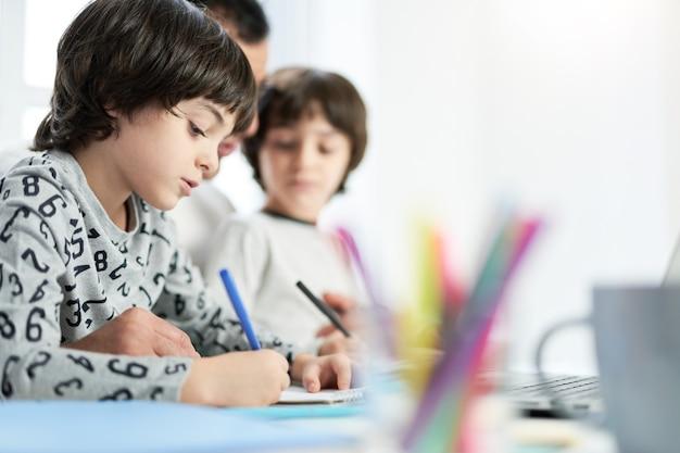 Skupiony mały latynoski chłopiec rysujący spędzając czas z tatą i bratem w domu. ojciec pracujący w domu i pilnujący dzieci. freelance, koncepcja rodziny