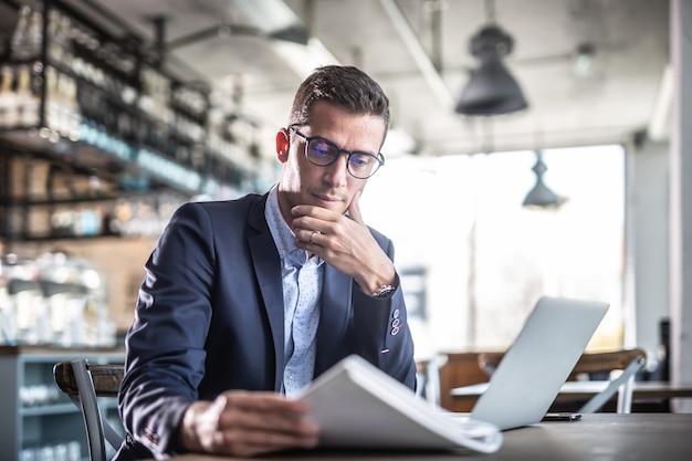 Skupiony mężczyzna czyta gazetę siedzi w pustej restauracji lub kawiarni w swoim biurowym ubraniu.