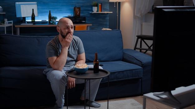 Skupiony mężczyzna ogląda dramat i płacze siedząc na kanapie jedząc popcorn