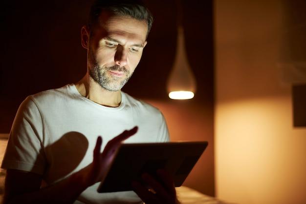 Skupiony mężczyzna używający tabletu w nocy