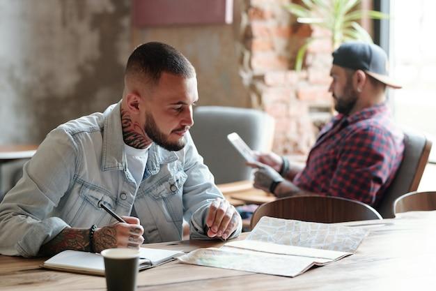 Skupiony młody brodaty mężczyzna siedzi przy stole w kawiarni i wybiera miejsca na papierowej mapie podczas planowania wakacji