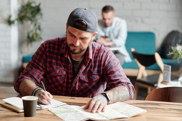 Skupiony młody brodaty mężczyzna z tatuażami siedzi przy drewnianym stole w kawiarni i robi notatki o zbliżającej się wyprawie w dzienniku