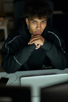 Skupiony młody facet z piercingiem siedzi przy stole przed monitorem komputera i pracuje z